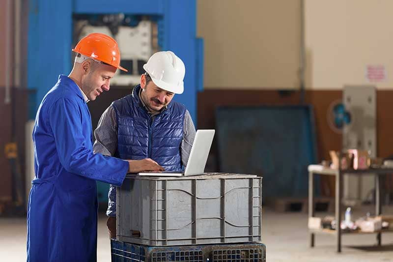 Young businessman and foreman working with laptop in factory.