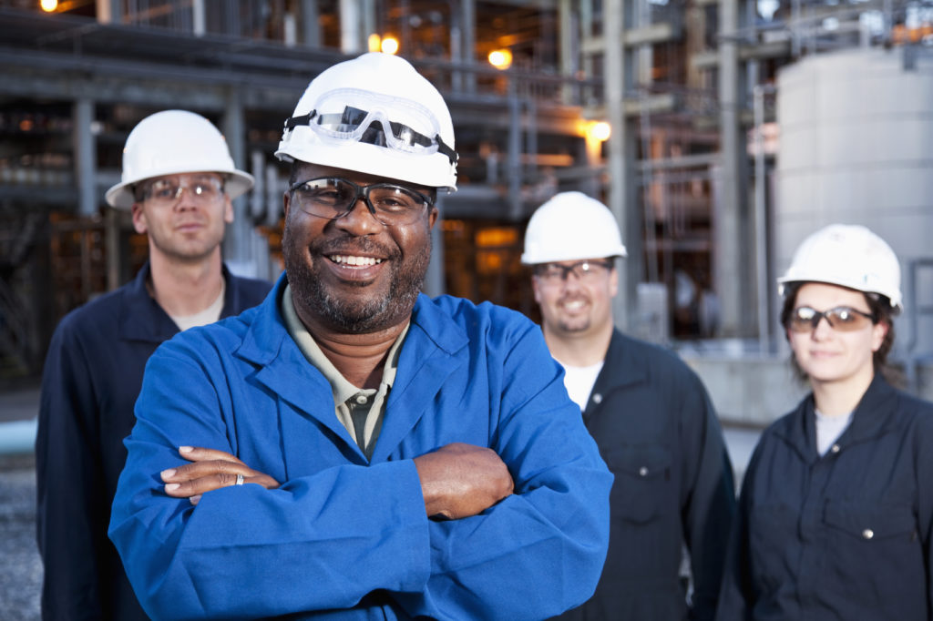 Multi-ethnic group of engineers working at a chemical plant.  Focus on African American man (50s) in foreground.